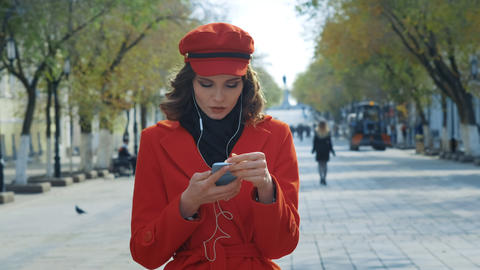 Elegant young girl in a red coat dances freely on the street. It takes pleasure Archivo