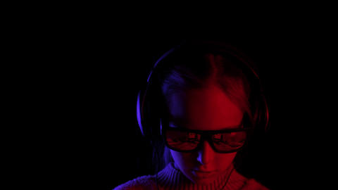 Girl in sunglasses and headphones browsing phone in darkness GIF