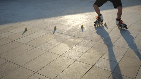Close-up legs of a young man professionally skating between cones on a nice ビデオ