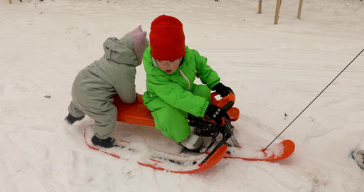 Cute kids in winter clothes riding sled together