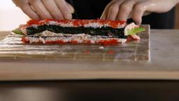 Close-up of Sushi making process.Rolls the sushi roll.Rice, nori, avocado, crab Archivo
