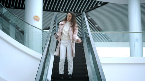 Beautiful young girl dancing freely in a shopping center on an escalator. Feels ビデオ