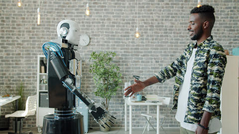Joyful African American man shaking hand to manlike robot in workplace Live Action