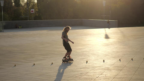 Young long-haired man roller skater is dancing between cones in the evening in a GIF