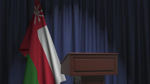 Flag of Oman and speaker podium tribune. Political event or statement related Live Action