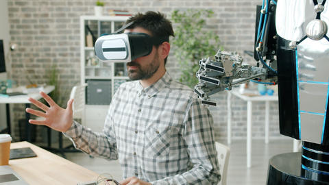 Scientist in virtual reality glasses moving hand and robot repeating movements Live Action