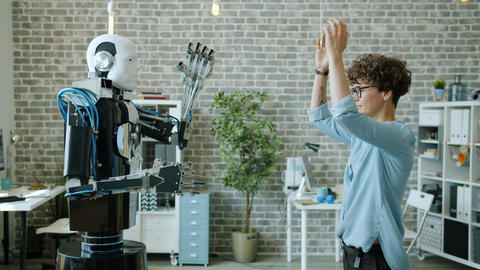 Smiling woman controlling robot testing response, machine copying movements Live Action