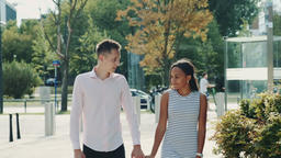 Multi-ethnic couple shyly looking at each other while walking the street ビデオ