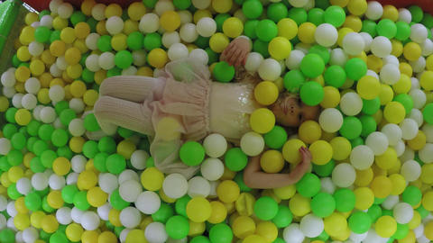 Active girl in pink dress playing in playground full of plastic colorful balls GIF