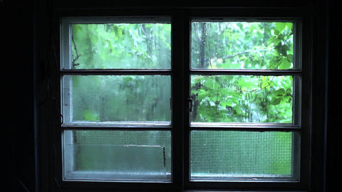Rainfall that falls down over a dark window from a dark room beyond which is see Live Action