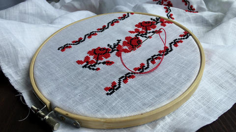 Traditional folk handmade cross-stitch floral pattern in the wooden hoop on the  Footage
