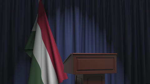 Flag of Hungary and speaker podium tribune. Political event or statement related Live Action