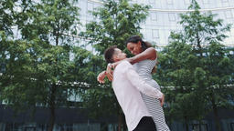 Cheerful boyfriend holding his mixed-race girlfriend in his hands and spinning GIF