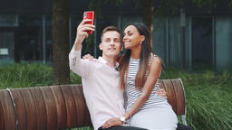 Cheerful young couple taking selfie sitting on bench outdoors ビデオ