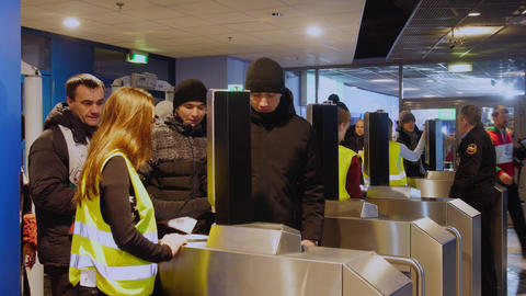 people pass turnstile for checking tickets coming to stadium GIF
