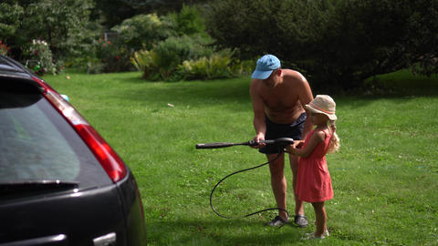 Dad and happy little girl washing car outdoor. Man with daughter have fun GIF