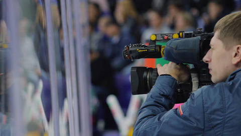 TV operator with camera shoots hockey game on ice rink ビデオ