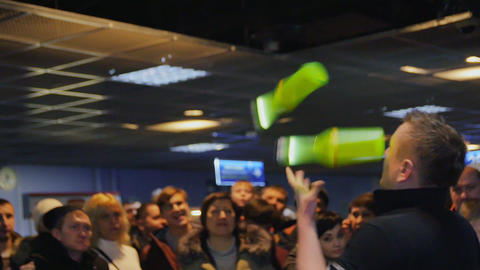 man joggles bottles entertaining people in stadium hall GIF
