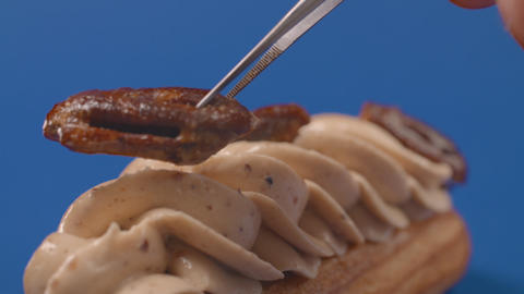 Confectioner adds pecans to the cream on eclair, cake decoration in slow motion Archivo