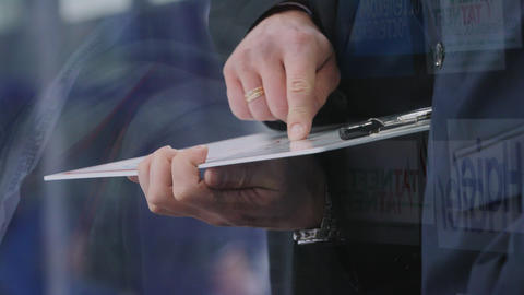 trainer with clipboard checks game plan closeup slow motion GIF