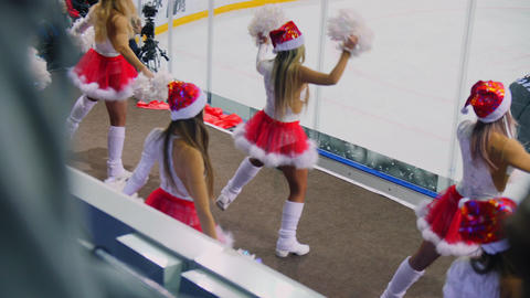 cheerleaders in Santa caps dance near ice rink backside view ビデオ