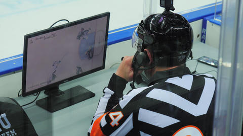 hockey judge watches match in office near ice arena backside ビデオ