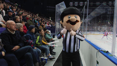 mascot person in hockey judge suit runs by modern ice arena Live Action