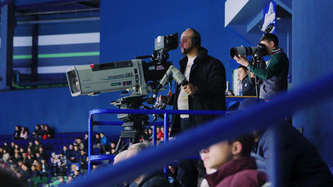 cameramen shoot hockey competition from tribunes on stadium GIF