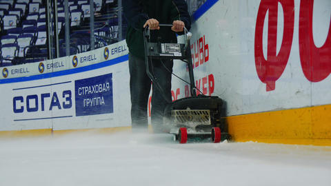 man cleans ice rink before hokey match with tool slow motion GIF