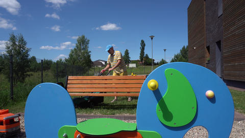 Young man mows lawn near children colorful playground. Gimbal movement GIF