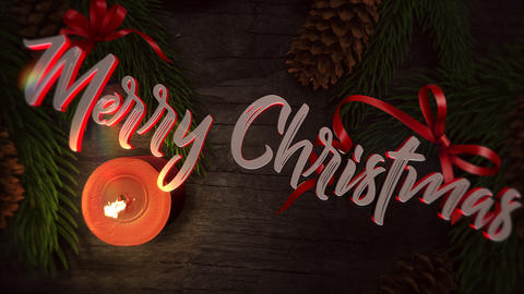Animated closeup Merry Christmas text, candle and green tree branches on wood background Animation