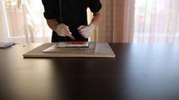 Male sushi chef puts red caviar tobiko on a rice and nori.Sushi making process Archivo