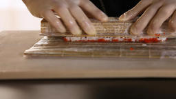 Close-up of chef's hands rolling a sushi roll on bamboo mat.Rice, nori, avocado Live Action