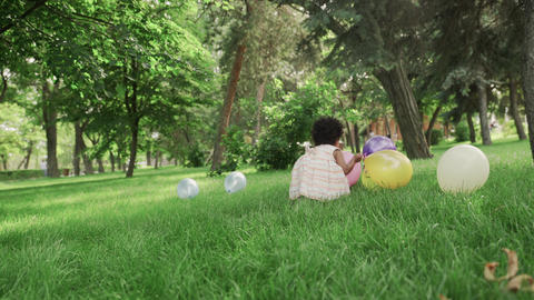 Little african-american girl play with multicolored balloons in the park GIF