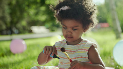 Little african-american girl play with brush and blue marker GIF
