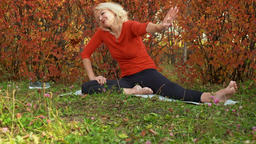 Smiling mature woman stretching on mat in autumn park GIF