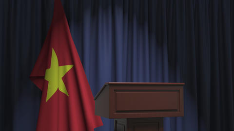 Flag of Vietnam and speaker podium tribune. Political event or statement related Live Action