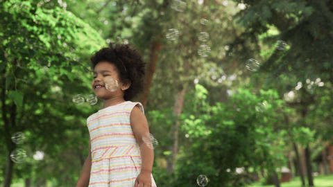 Little african-american girl play with soap bubbles in the park GIF