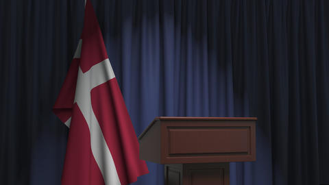 Flag of Denmark and speaker podium tribune. Political event or statement related Live Action
