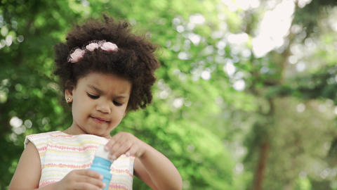 Close up of african-american girl blow soap bubbles in the park GIF
