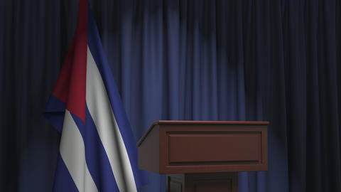 Flag of Cuba and speaker podium tribune. Political event or statement related Live Action