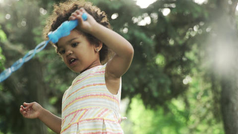 Little african-american girl plays with soap bubbles in the park GIF