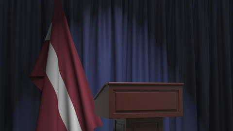 Flag of Latvia and speaker podium tribune. Political event or statement related Live Action