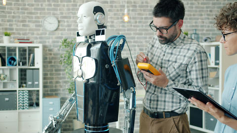 Male and female developers testing robot with modern devices working in office Live Action