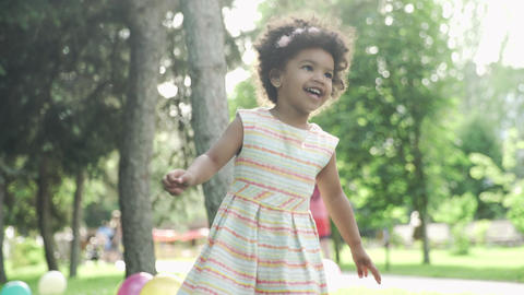 Little african-american girl plays and jumps in the park. Unrecognizable people GIF