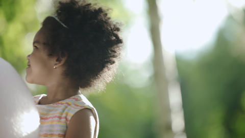Little african-american girl with diadem on head eating cotton candy GIF