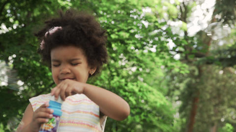 Little african-american girl blow soap bubbles in the park GIF