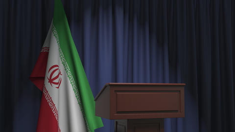 Flag of Iran and speaker podium tribune. Political event or statement related Live Action