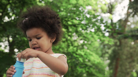 Little and cute african-american girl blows soap bubbles in the park GIF