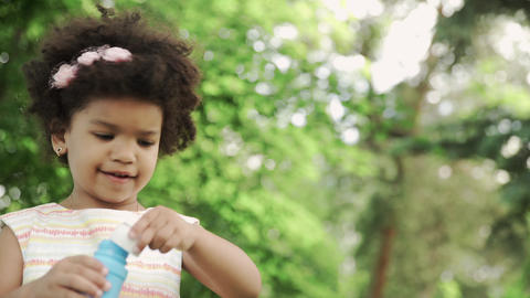 Little and cute african-american girl blow soap bubbles in the park GIF